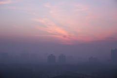 在日落的城市地平线,许多烟雾和坏生态 库存照片