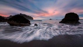 在日落的多岩石的海滩风景 免版税图库摄影