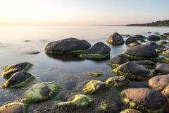 在日落的多岩石的海滩用乳状水 免版税库存照片