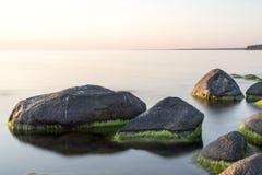 在日落的多岩石的海滩用乳状水 库存图片
