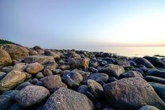 在日落的多岩石的海滩用乳状水 免版税图库摄影