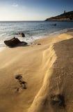 在日落的多岩石的海滩 免版税库存图片