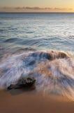在日落的多岩石的海滩 免版税图库摄影