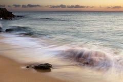 在日落的多岩石的海滩 库存图片