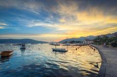 在日落的天空在真珠色的水表面反射,偏僻的小船漫步 库存图片