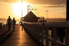 在日落的夫妇在码头 库存图片
