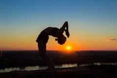 在日落的女子实践的瑜伽-滴下,轮子姿势 免版税图库摄影