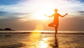 在日落的女子实践的瑜伽 图库摄影
