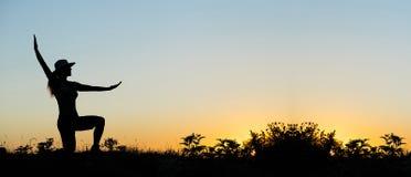 在日落的女性剪影 图库摄影