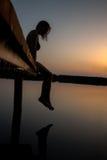 在日落的妇女剪影在木船坞 免版税库存图片