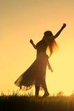 在日落的妇女跳舞 免版税库存照片