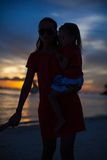 在日落的妈妈和女儿剪影在 库存图片
