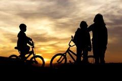 在日落的妈妈和孩子债券。 免版税库存图片