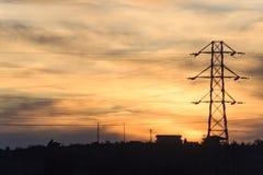 在日落的定向塔和村庄剪影 库存图片