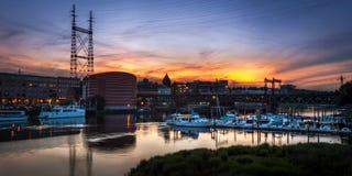 在日落的小游艇船坞和火车桥梁 免版税库存照片
