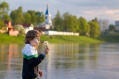 在日落的小男孩吹的蒲公英在河岸 免版税库存照片