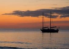 在日落的小船剪影 图库摄影