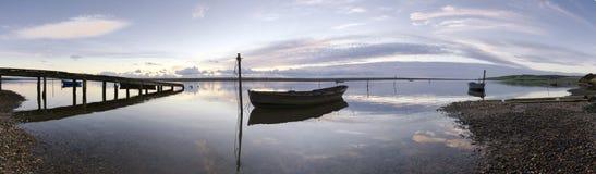 在日落的小船和跳船 库存图片