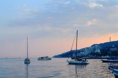 在日落的小船在雅尔塔克里米亚俄罗斯港的黑海  免版税图库摄影
