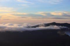 在日落的山横向 从山峰在高岩石蓝天云彩和海的惊人的看法在晚上 低的云彩 免版税库存图片