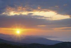 在日落的山横向 从山峰的惊人的看法在岩石、低云、蓝天和海在晚上 五颜六色 库存图片