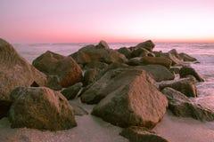 在日落的岩石在海湾 免版税图库摄影