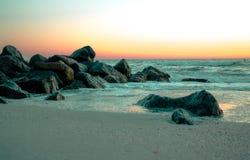 在日落的岩石在海湾 库存照片