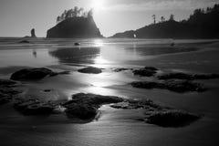 在日落的岩石沿海海滩 库存图片