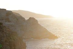 在日落的岩石海岸 免版税库存照片