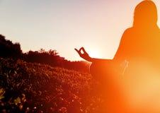 在日落的平静和瑜伽实践 免版税库存图片