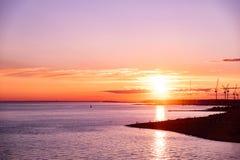 在日落的建筑用起重机由海 库存照片