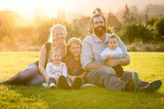 在日落的微笑的家庭 免版税库存照片