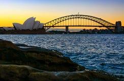 在日落的悉尼歌剧院和港口桥梁 免版税库存图片