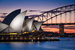 在日落的悉尼歌剧院和港口桥梁 库存照片