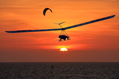 在日落的悬挂式滑翔机 库存照片