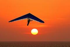 在日落的悬挂式滑翔机 免版税库存照片