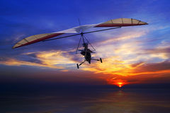 在日落的悬挂式滑翔机 库存图片