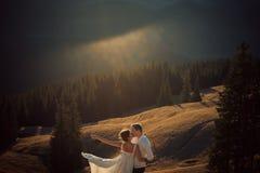 在日落的愉快的婚礼夫妇亲吻在山 蜜月 免版税库存图片