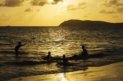 在日落的愉快的家庭游泳 免版税图库摄影
