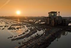 在日落的拖拉机与太阳 免版税库存图片