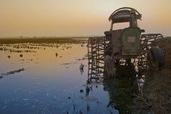 在日落的拖拉机在水 库存图片