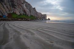 在日落的斑斑沙子样式在Morro在加利福尼亚中央海岸晃动在莫罗贝加利福尼亚美国 免版税库存图片