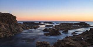 在日落的新月形海湾海滩 免版税库存图片