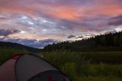 在日落的旅游帐篷在山谷,在黑暗的天空的暴风云 库存图片