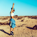 在日落的时髦的被晒黑的女孩跳舞在沙漠 免版税库存照片