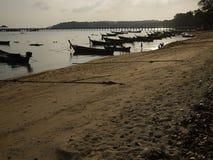 在日落的普吉岛Thialand海滩在传统小船附近哄骗使用在水中 库存图片