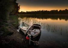 在日落的木划艇 免版税库存图片