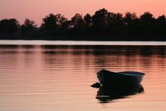 在日落的木小船 免版税库存照片