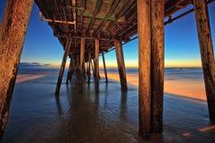 在日落的木海滩码头下,皇家海滩,加利福尼亚 免版税库存照片
