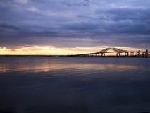 在日落的桥梁在江边或更新的海湾 免版税库存图片